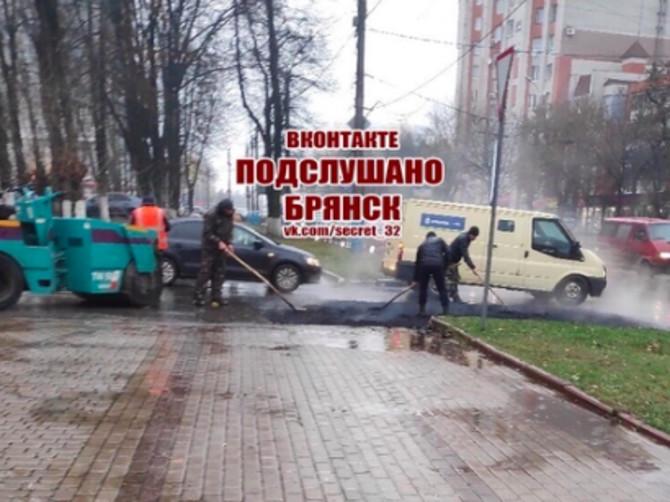 В Брянске у площади Партизан рабочие укладывают асфальт во время дождя