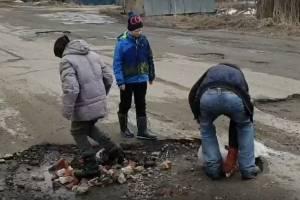 В Белых Берегах подростки сами заделали ямы на дорогах